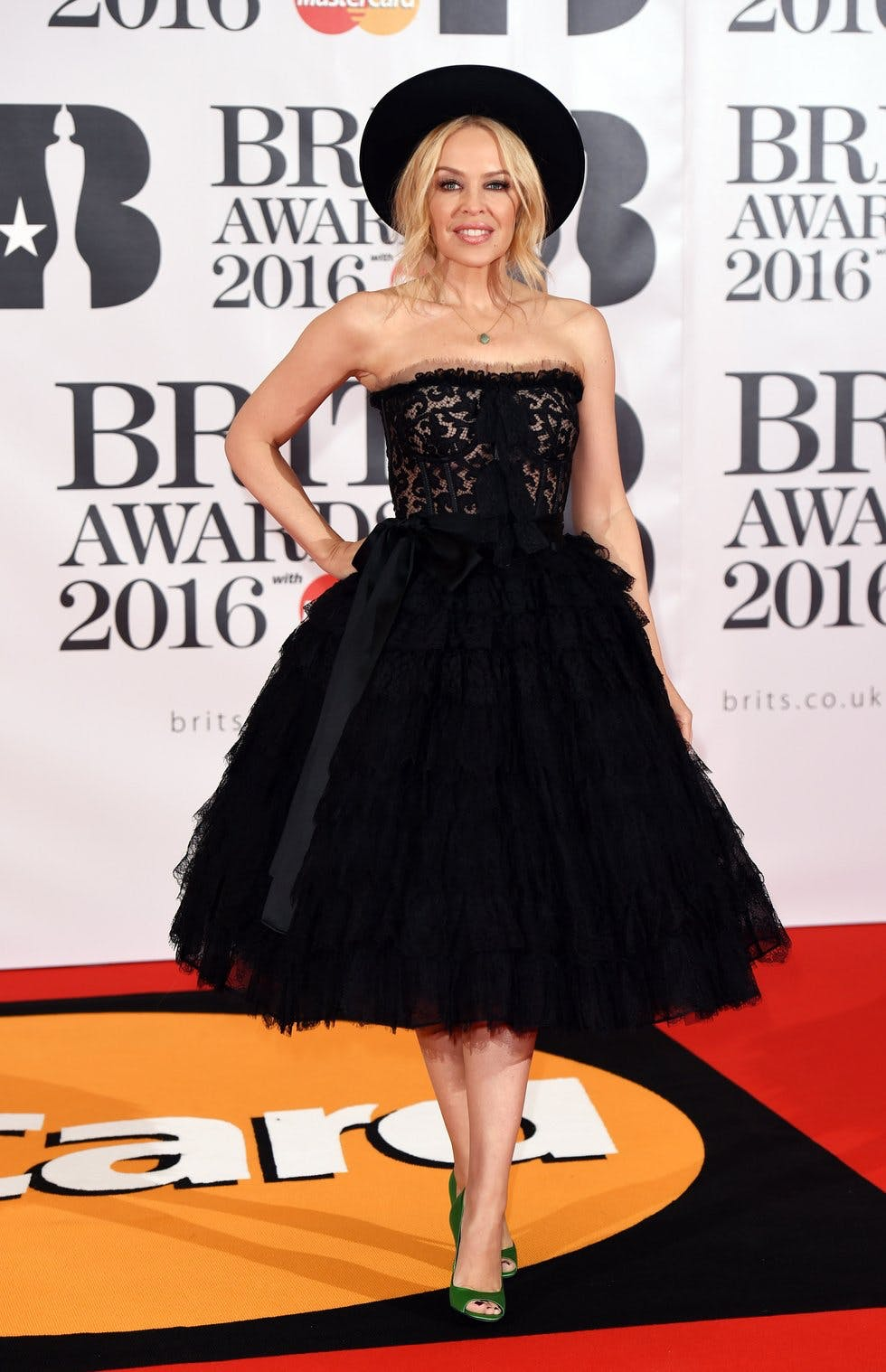 Kylie tops off a full-skirted black Dolce and Gabbana dress with a black  trilby at the BRIT Awards in London. fcff418a9