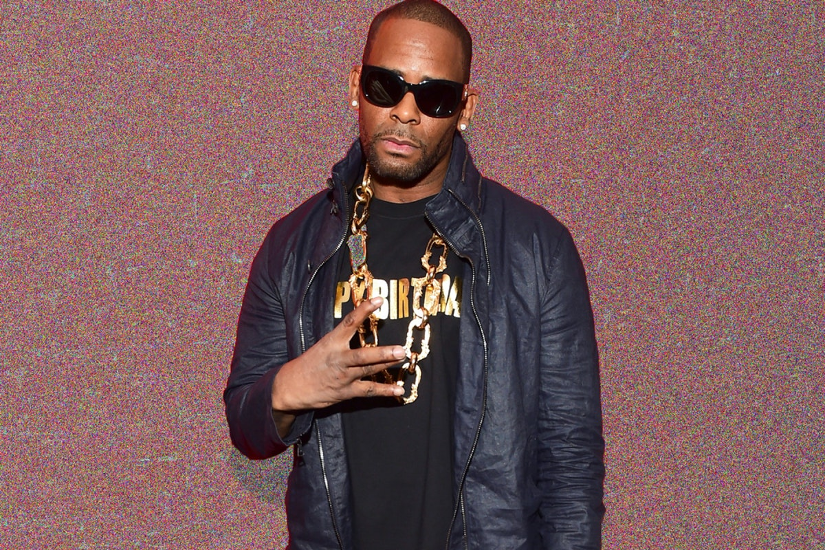 R Kelly wearing a leather jacket and sunglasses, standing against a tan glittery background