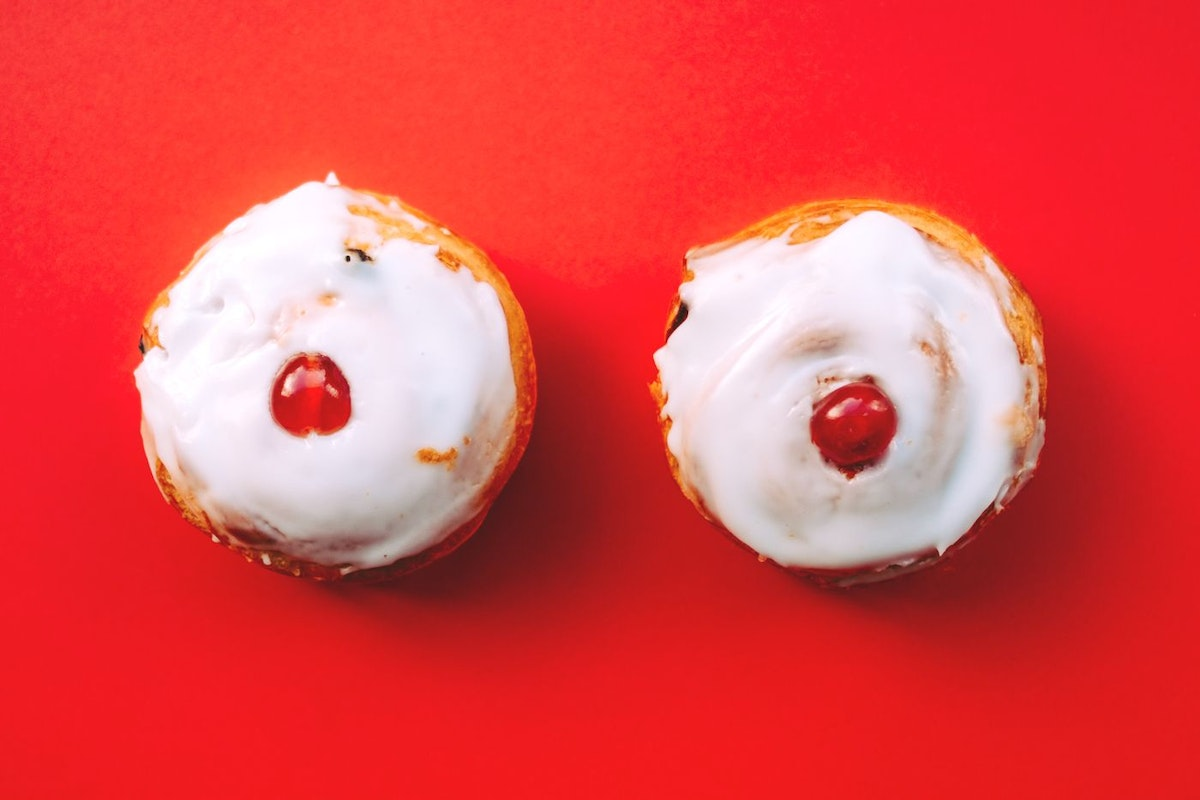 A photograph of two iced cherry buns on a red background