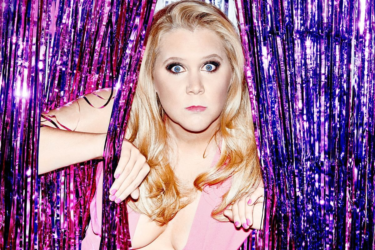 Amy Schumer peeks through a purple fringe curtain