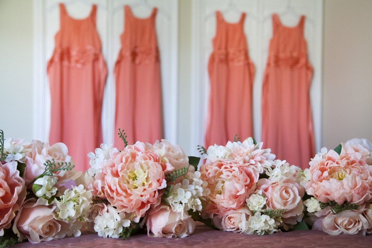 Four coral bridesmaid dresses hanging up on a wardrobe door