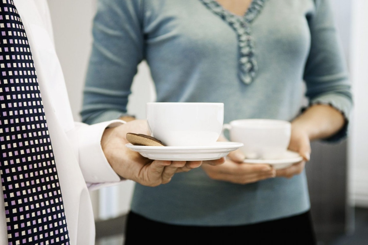 Women drinking coffee together in an office