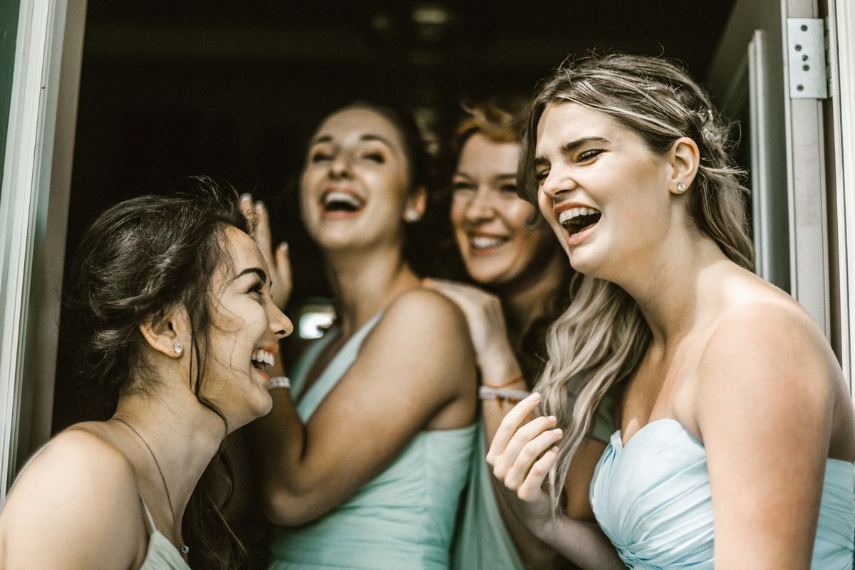 A bride and her bridesmaids share a laugh before the wedding