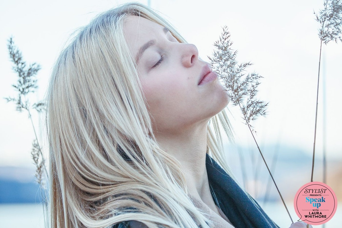 A blonde woman sniffs a blade of grass in a wintry landscape