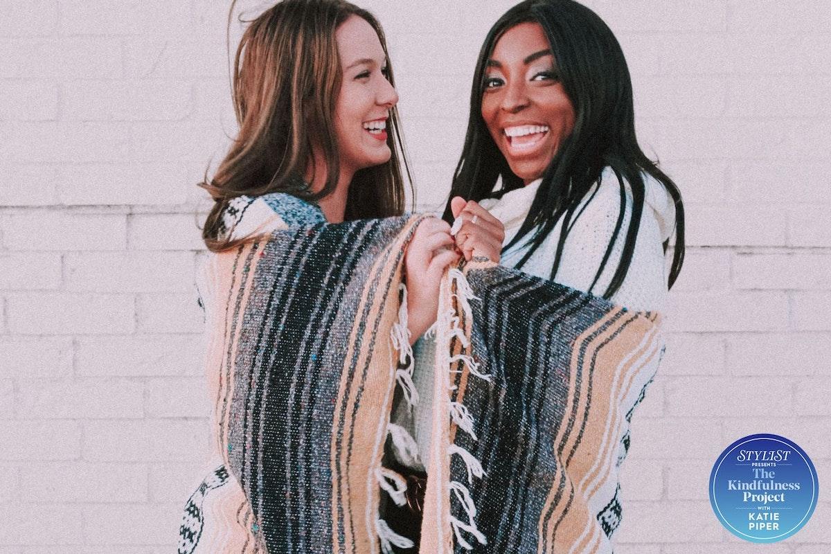 Two women in blankets smiling