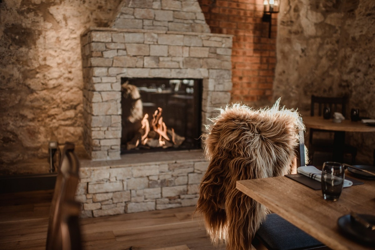 A roaring stone fire with a furry blanket draped on a chair